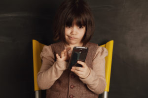 portrait of a cute little girl with a smart phone